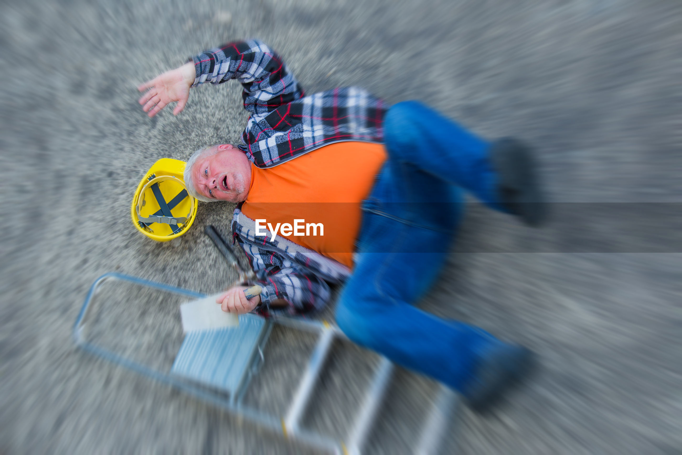 Blurred motion of man fallen on road by ladder and hardhat