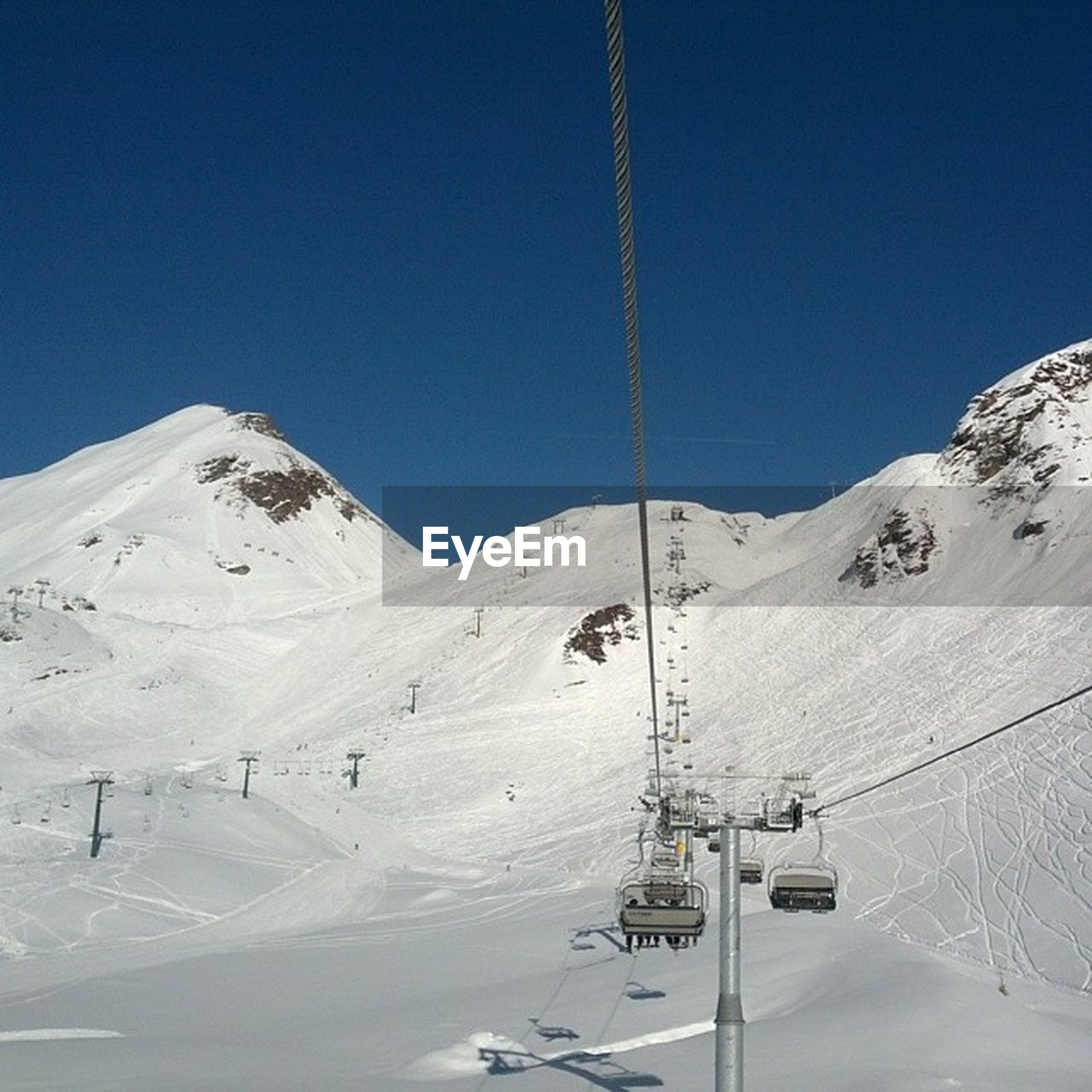 snow, winter, cold temperature, mountain, season, snowcapped mountain, clear sky, mountain range, blue, tranquility, tranquil scene, landscape, scenics, beauty in nature, weather, covering, nature, copy space, overhead cable car, non-urban scene