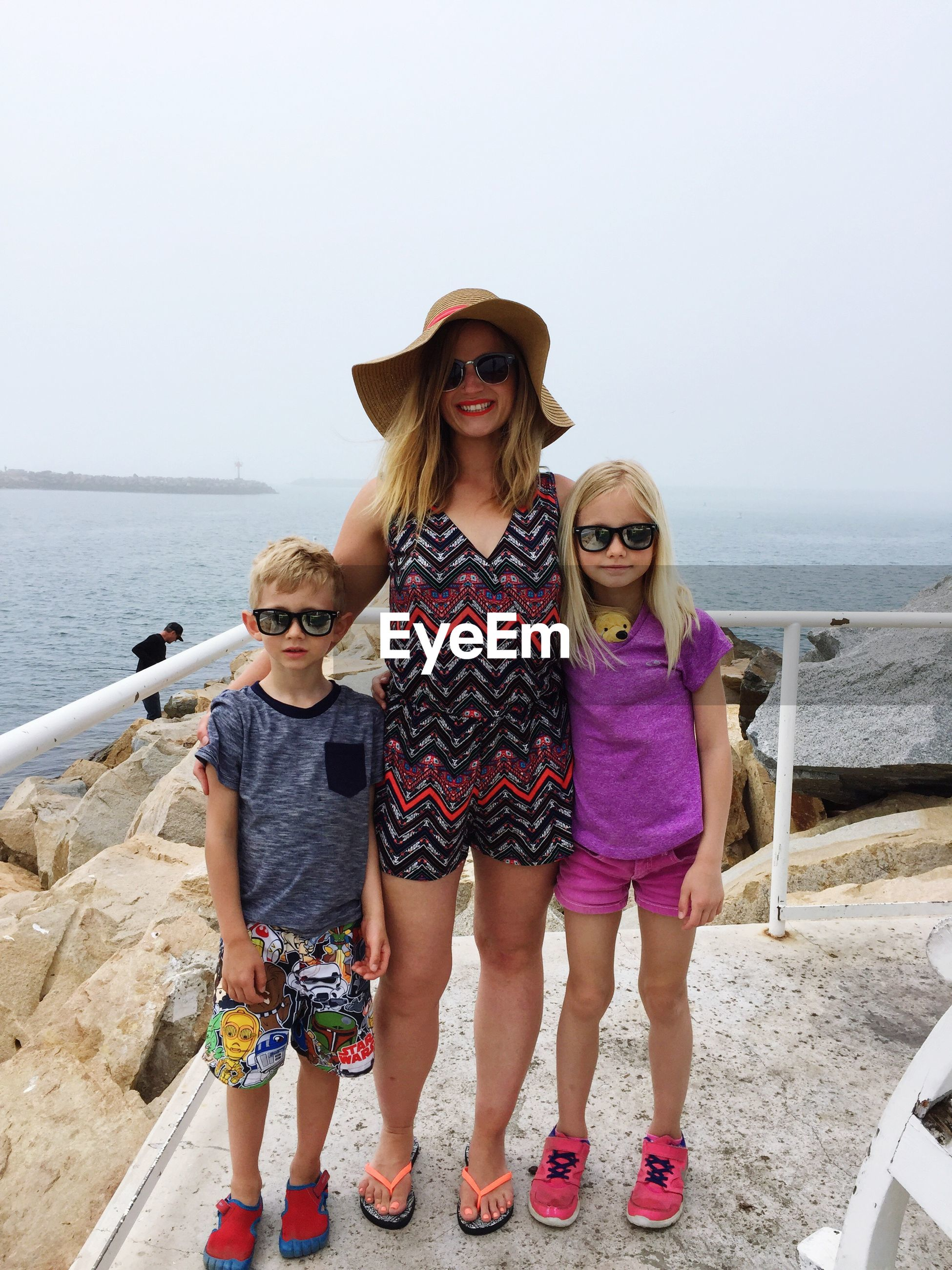 Portrait of happy mother with children standing on walkway against sky