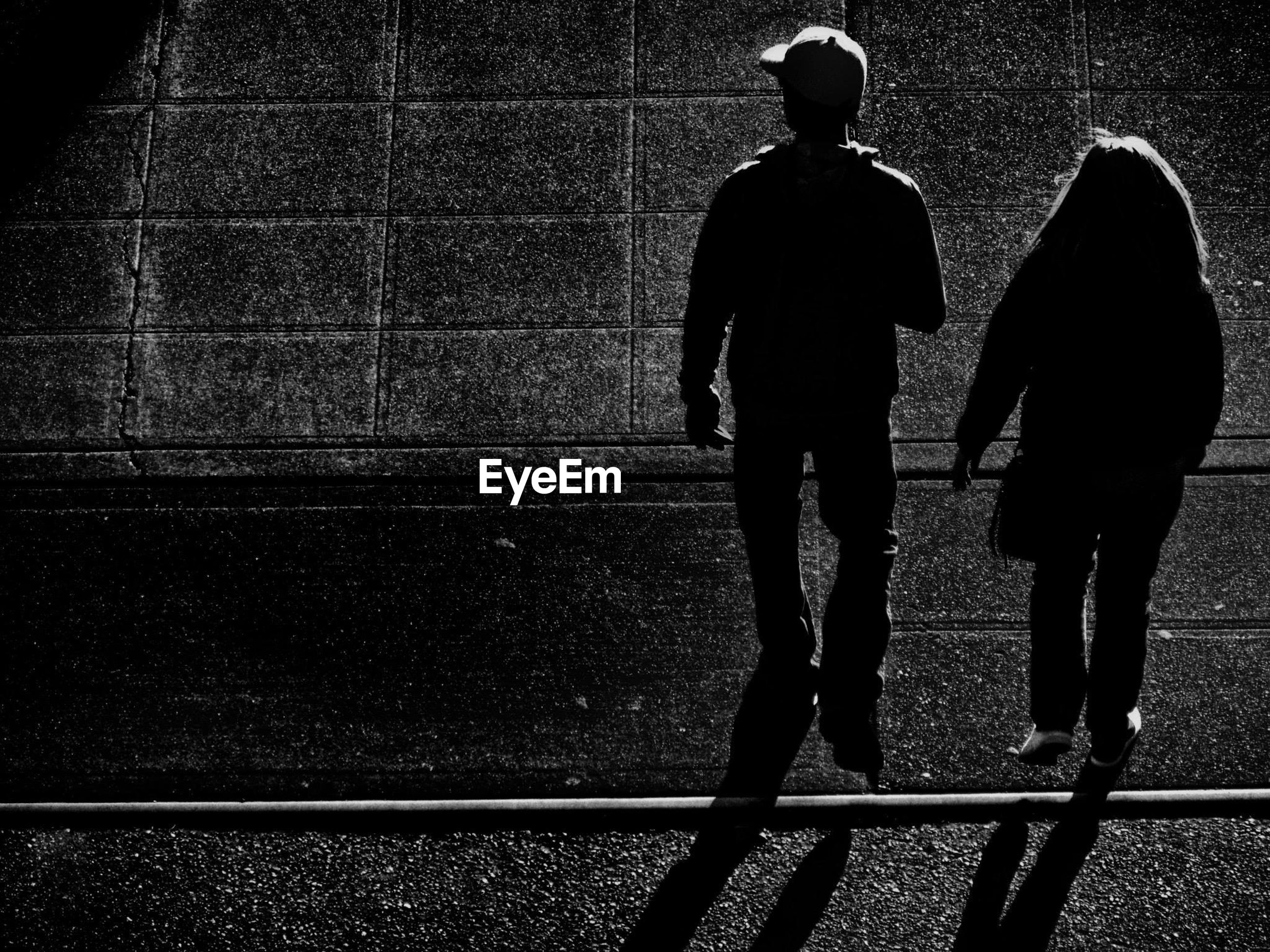 Full length rear view of silhouette man and woman standing on street at night