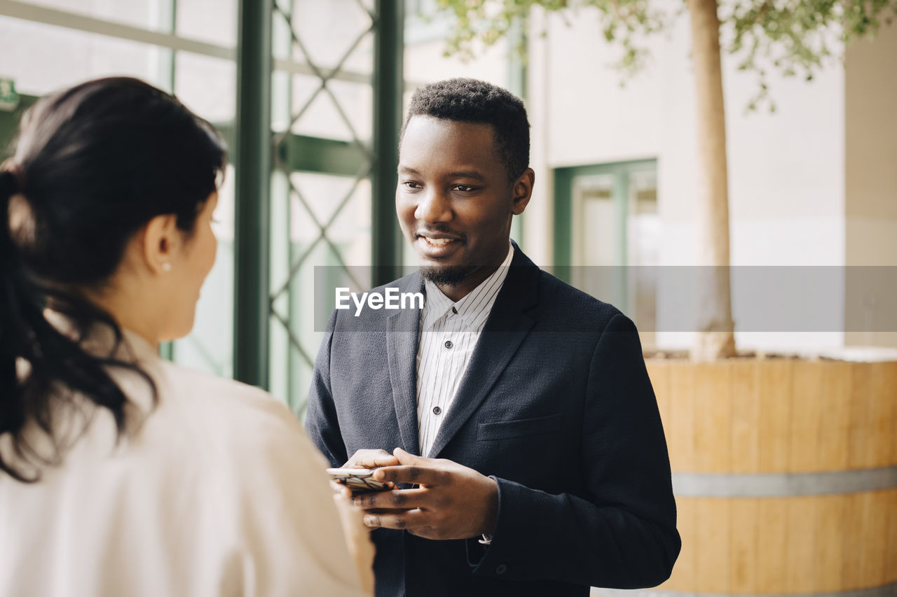 Businessman communicating with female coworker in meeting at office