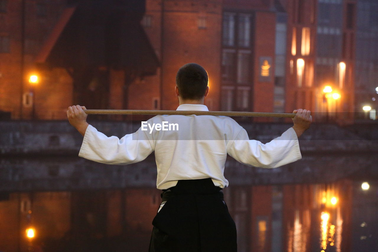 Rear view of man practicing martial arts while standing against canal in city during sunset