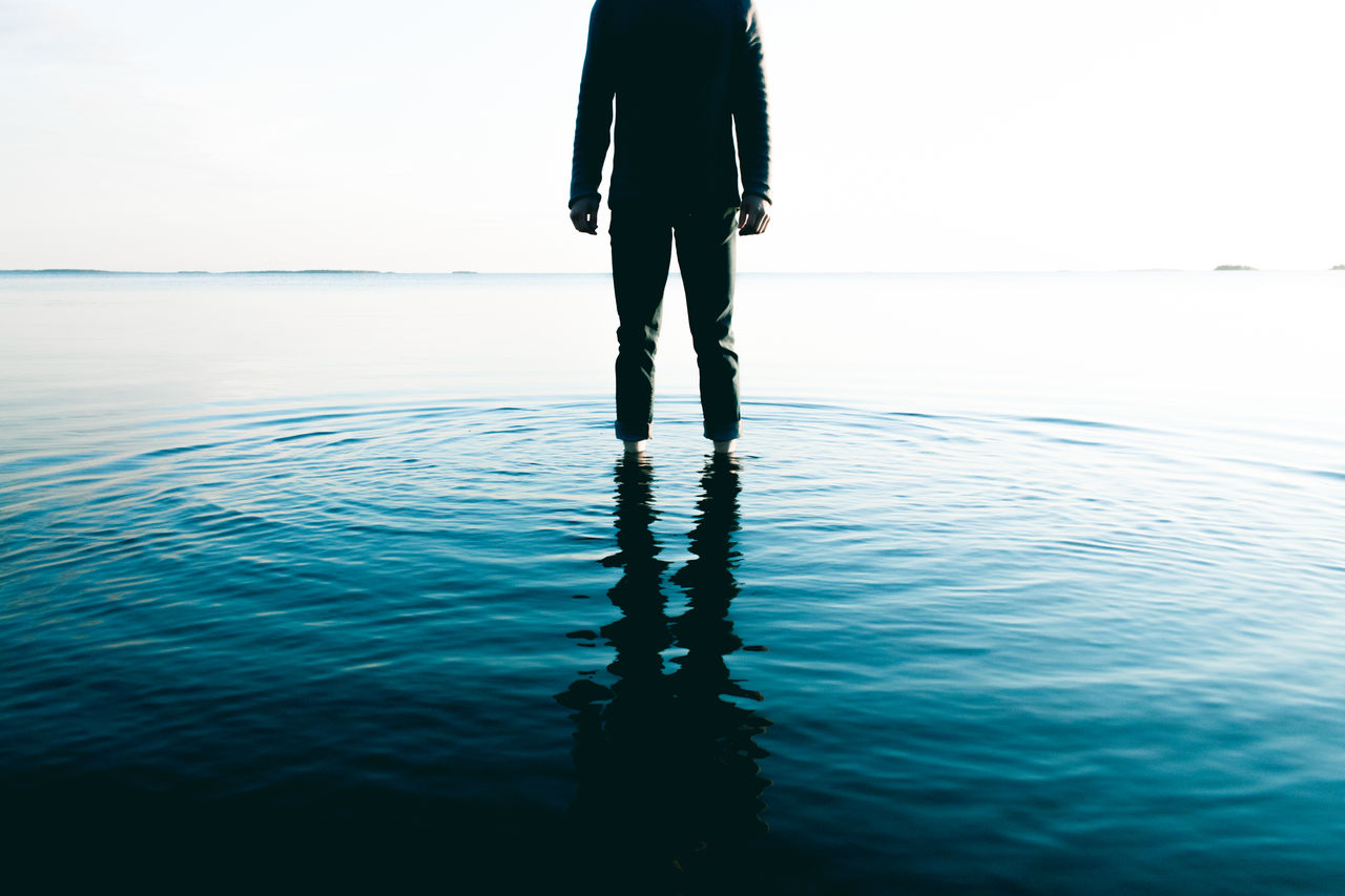 Low section of man standing in sea against sky