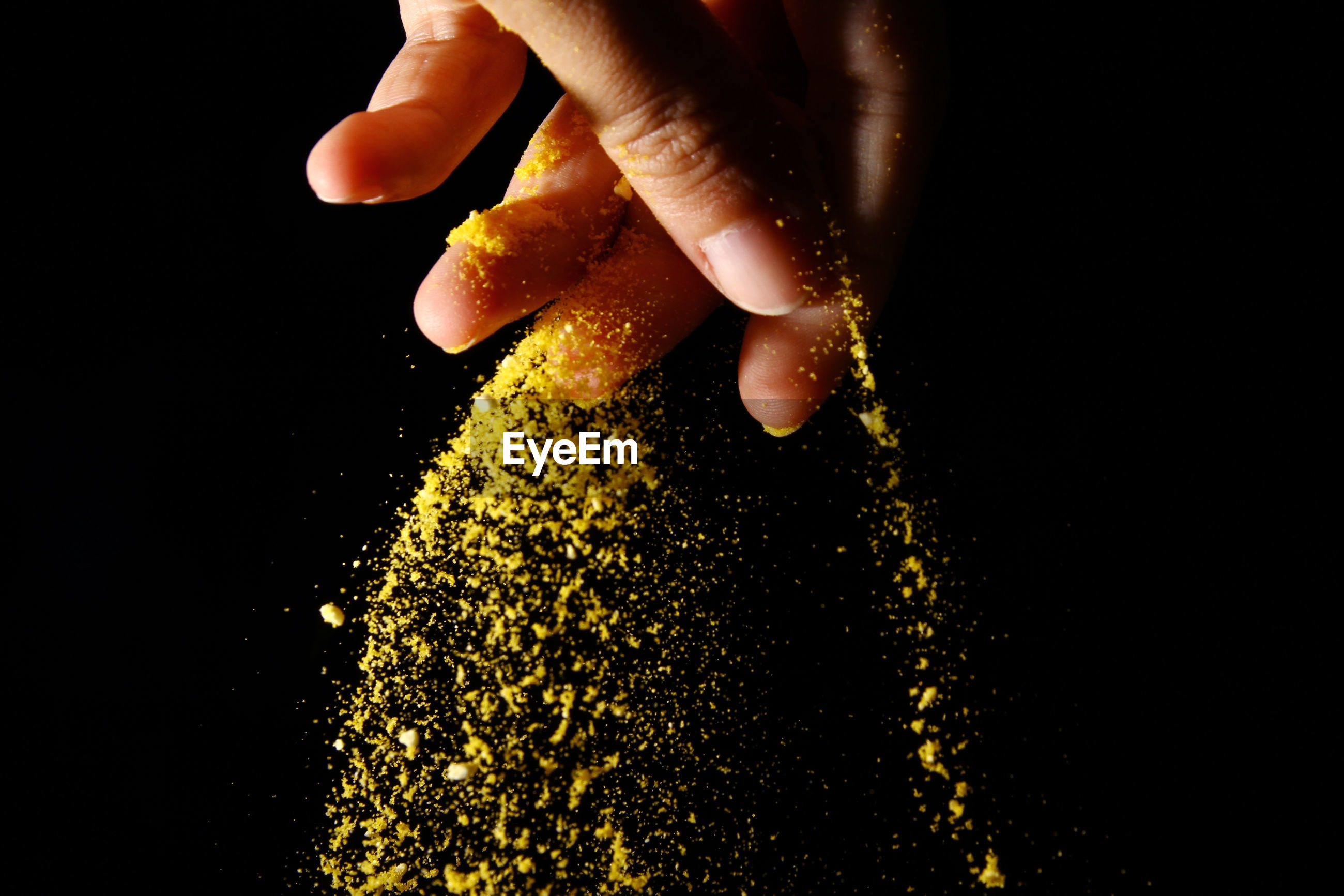 Close-up of hand sprinkling powder paint against black background