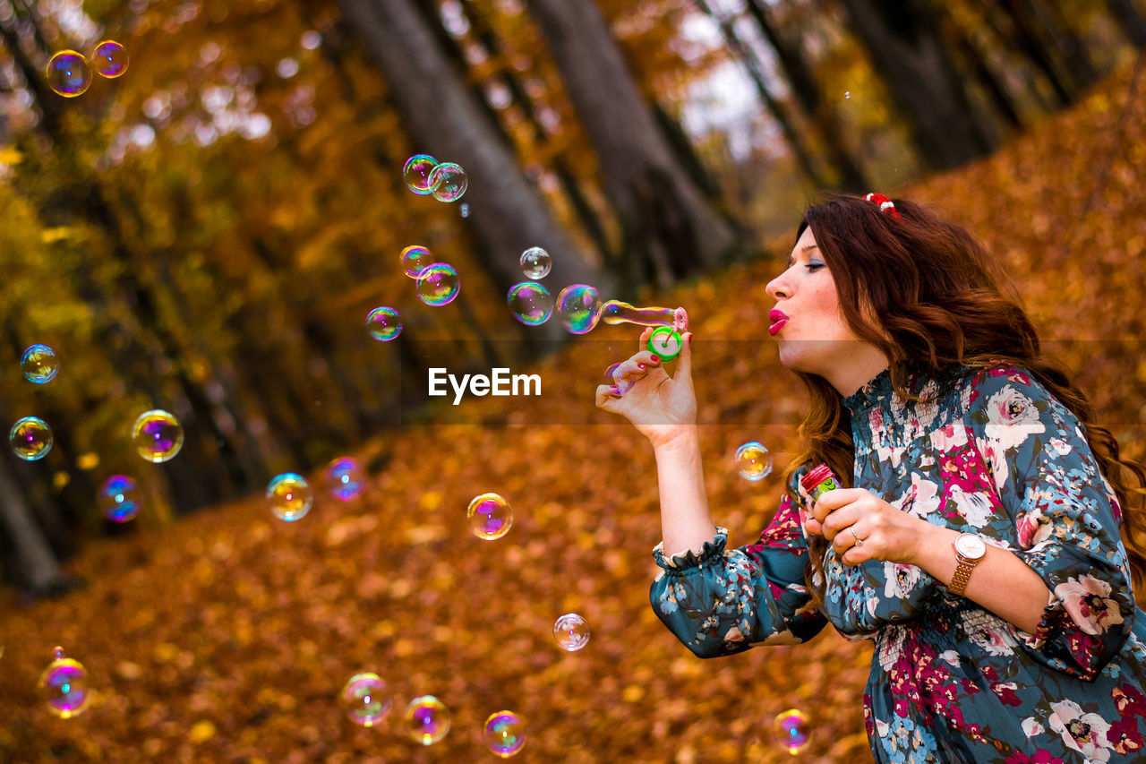Mid Adult Woman Blowing Bubbles In Forest During Autumn