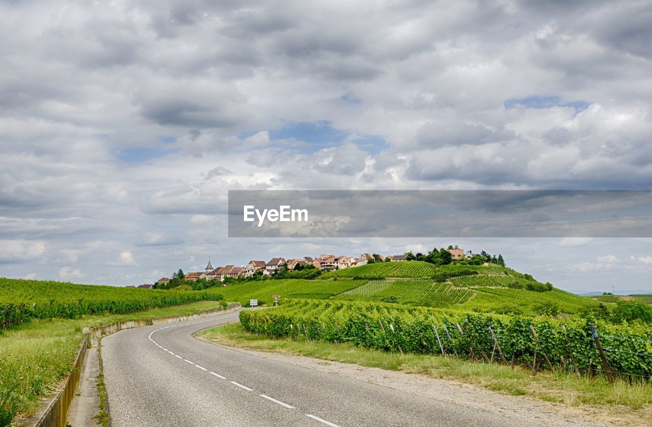 cloud - sky, sky, the way forward, road, green color, landscape, nature, scenics, beauty in nature, tranquility, field, no people, day, outdoors, tranquil scene, rural scene, agriculture, transportation, grass, travel destinations, tree, winding road