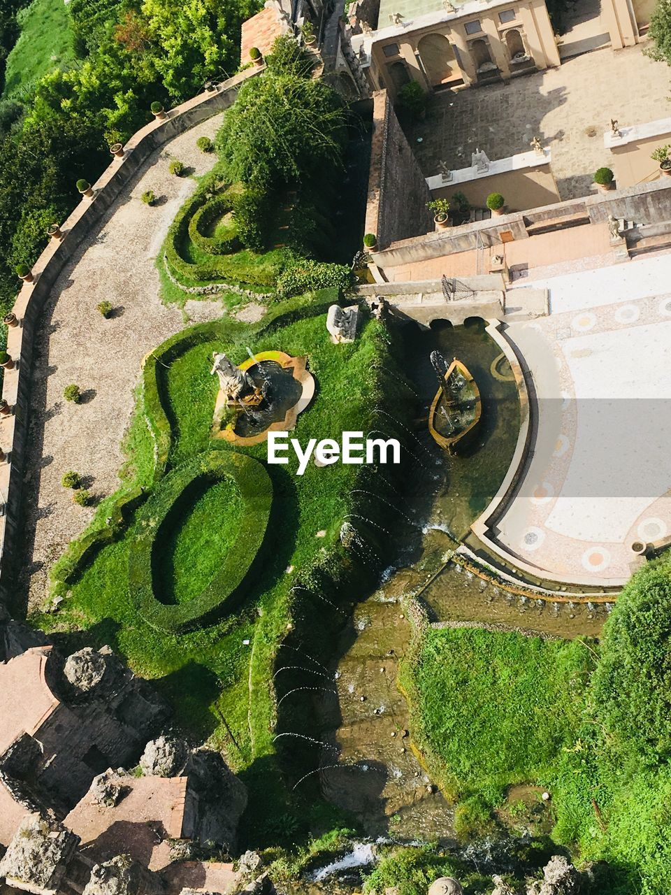 plant, high angle view, day, green color, nature, architecture, water, no people, built structure, grass, sunlight, growth, outdoors, old, garden, building exterior, moss, tree, formal garden, wheel
