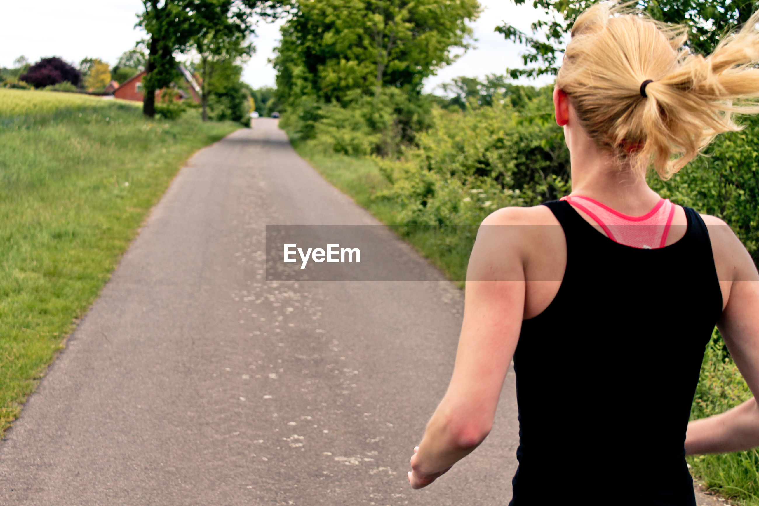 Rear view of a woman jogging on pathway