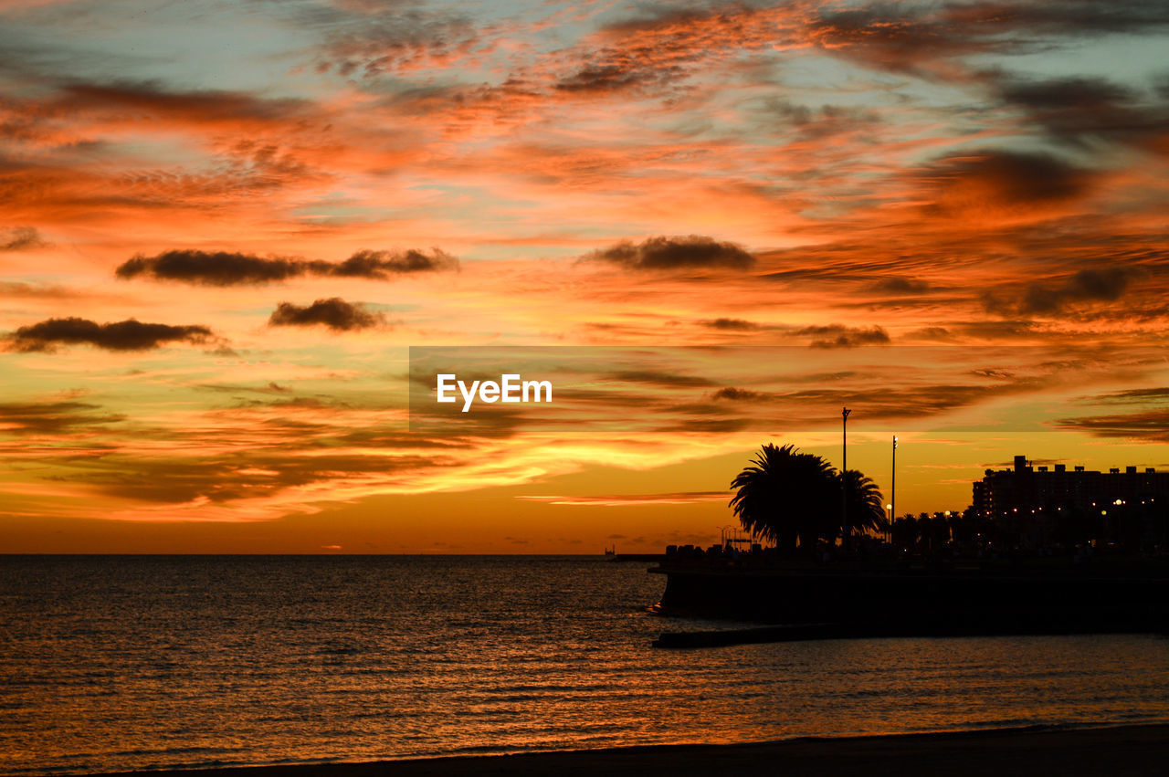 sunset, sea, water, sky, orange color, scenics, beauty in nature, tranquility, cloud - sky, dramatic sky, tranquil scene, silhouette, nature, horizon over water, idyllic, tree, no people, beach, outdoors, waterfront, built structure, building exterior, travel destinations, palm tree, architecture