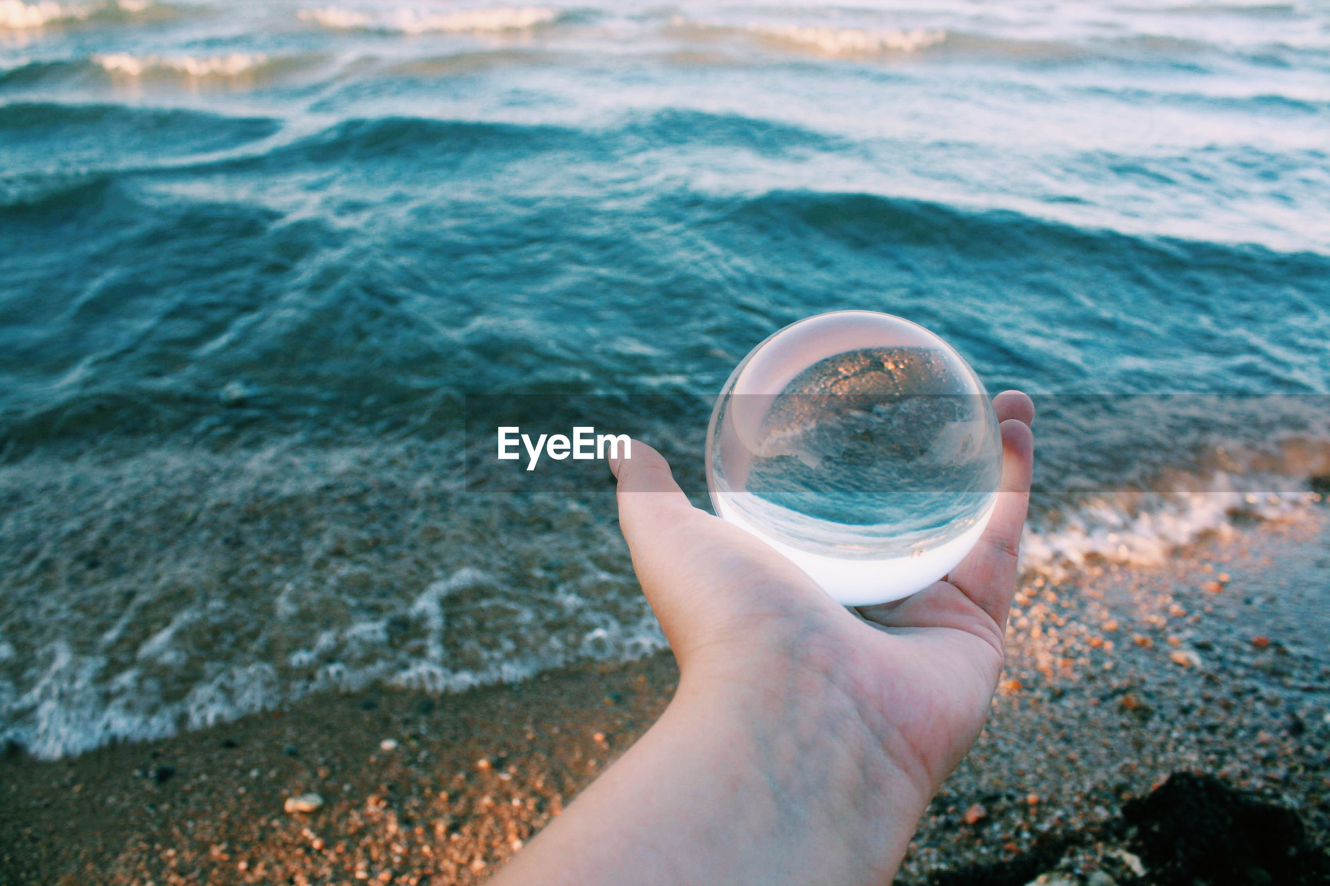 Cropped hand holding crystal ball against sea