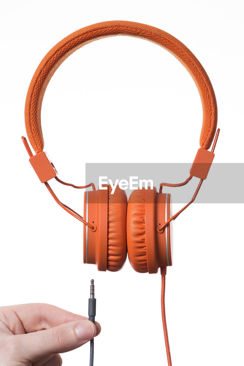 Close-up of hand holding headphones against white background