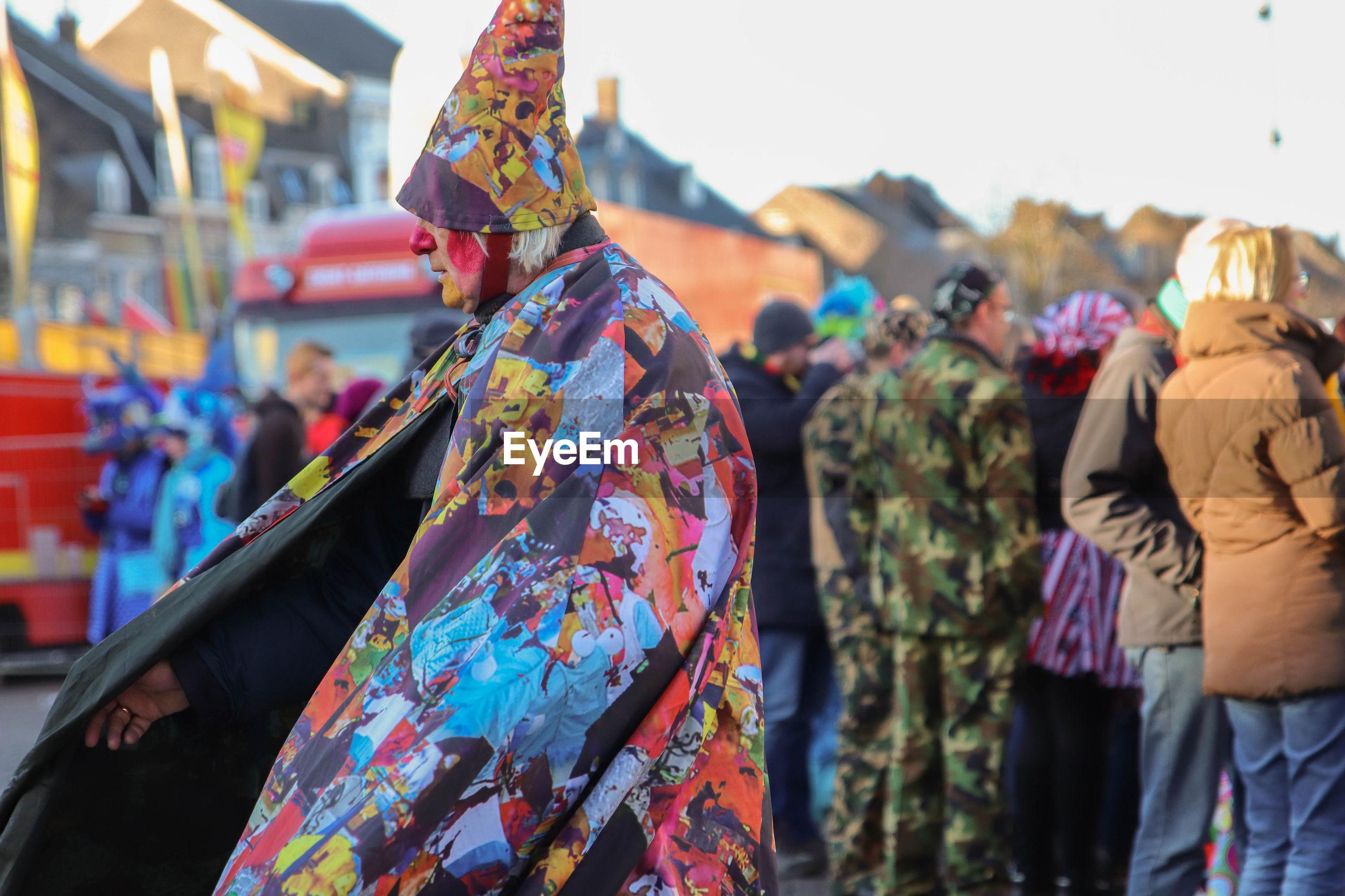 REAR VIEW OF WOMEN STANDING IN STREET