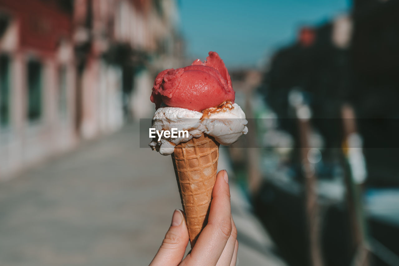 sweet, human hand, ice cream, dairy product, food, sweet food, holding, frozen food, hand, unhealthy eating, food and drink, one person, focus on foreground, dessert, human body part, ice cream cone, cone, real people, indulgence, frozen, temptation, finger, body part, outdoors, frozen sweet food, nail