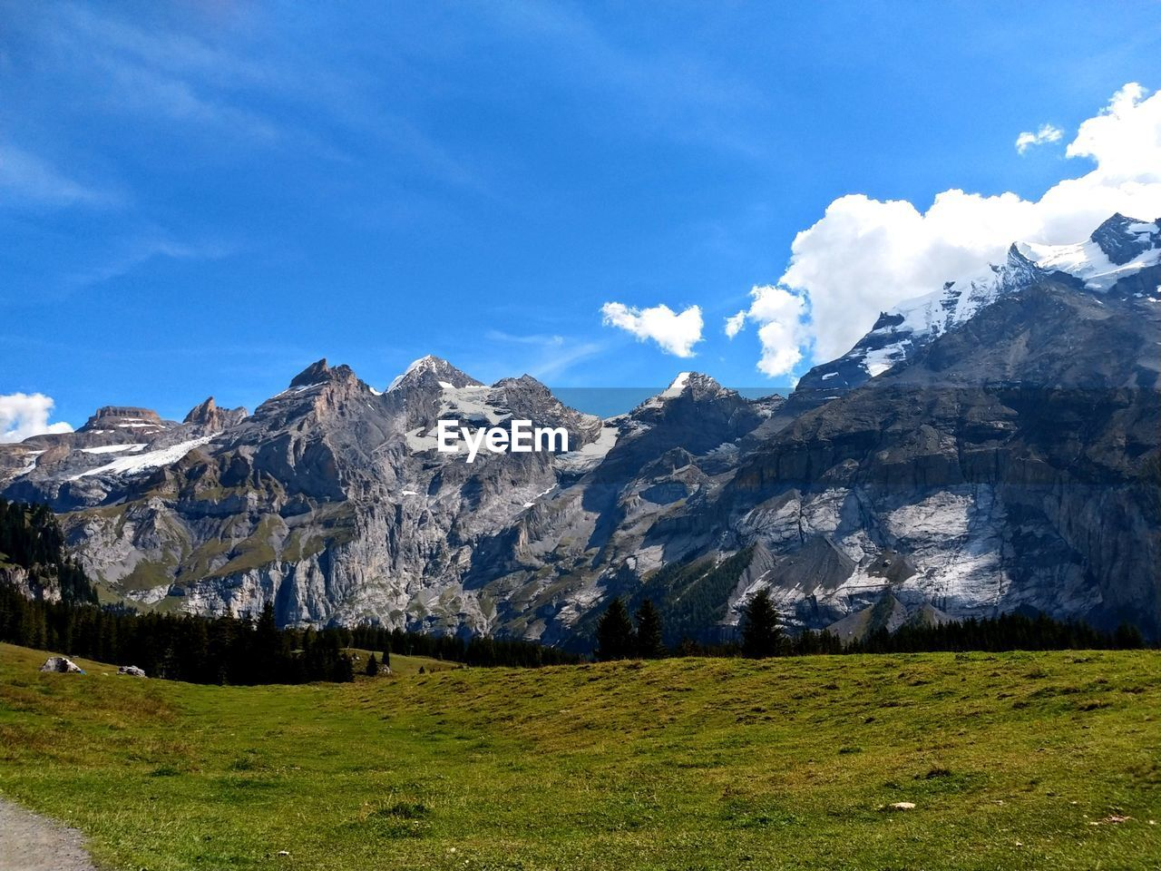 mountain, sky, landscape, grass, environment, cloud - sky, nature, beauty in nature, tranquil scene, land, tranquility, scenics - nature, plant, no people, snow, scenery, day, field, non-urban scene, green color, mountain peak, range, mountain range, snowcapped mountain