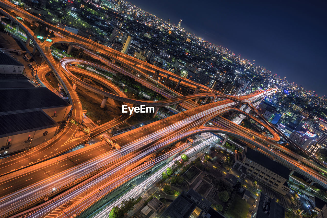 High angle view of light trails on elevated road in illuminated city at night