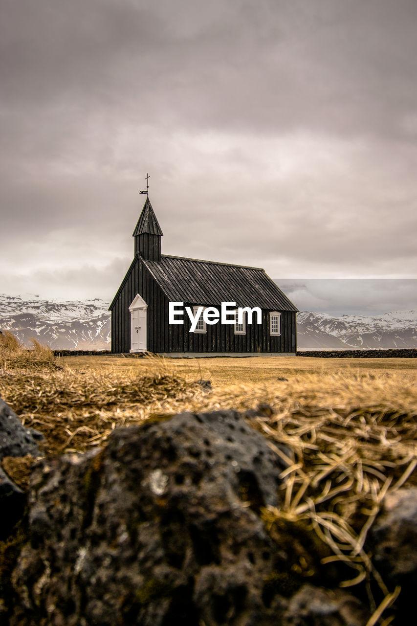 Chapel on field against cloudy sky
