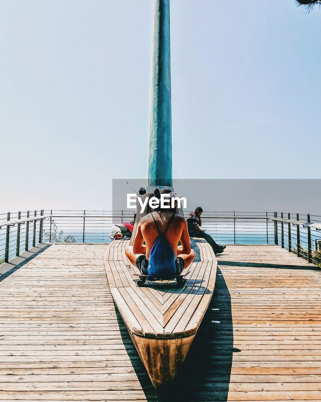 sky, water, real people, railing, lifestyles, leisure activity, nature, day, nautical vessel, transportation, one person, wood - material, clear sky, pier, casual clothing, sea, women, architecture, outdoors