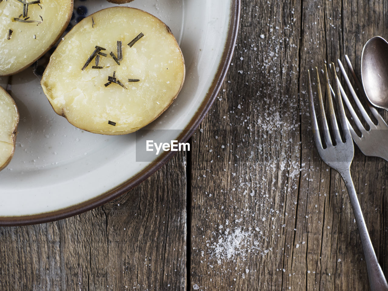 Directly above view of baked potatoes with rosemary in plate by cutlery on wooden table