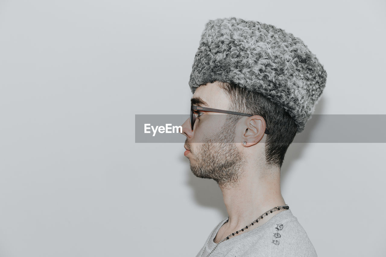 studio shot, one person, headshot, beard, glasses, indoors, young adult, gray, young men, portrait, eyeglasses, facial hair, side view, close-up, copy space, white background, clothing, men, human face, contemplation, profile view