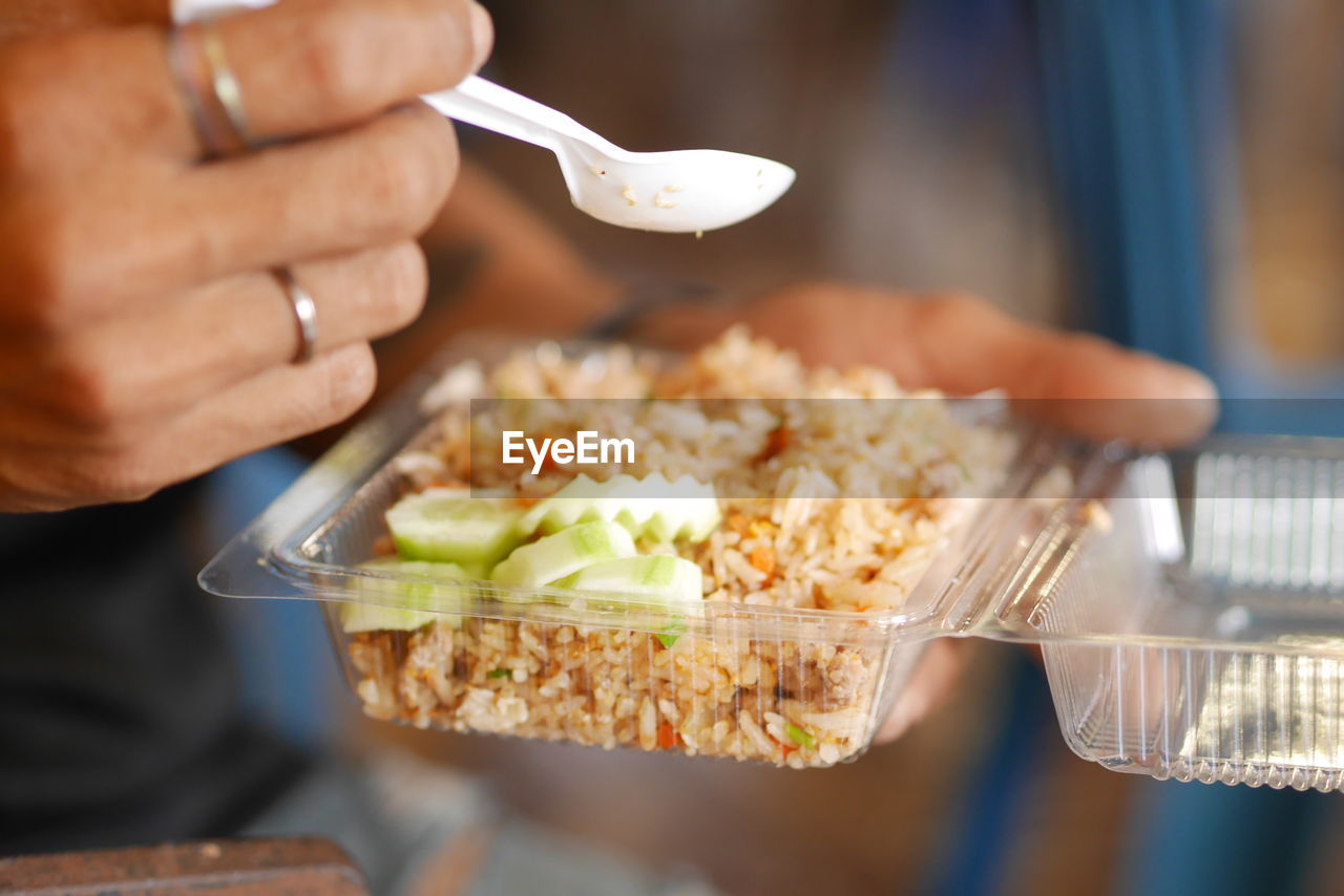 Close-up of person holding food in plastic container