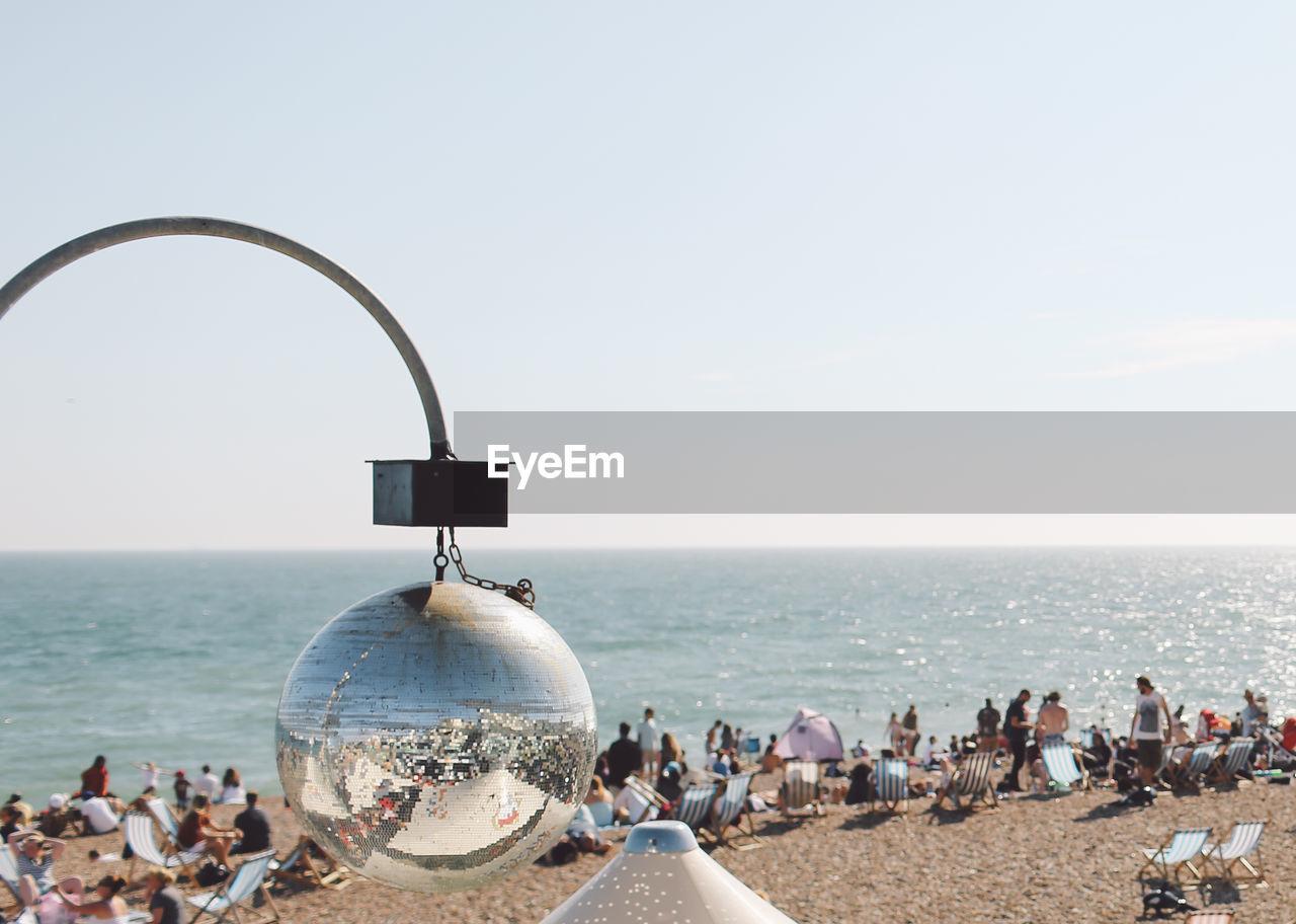 Reflection Of Brighton Beach On Disco Ball Against Clear Sky