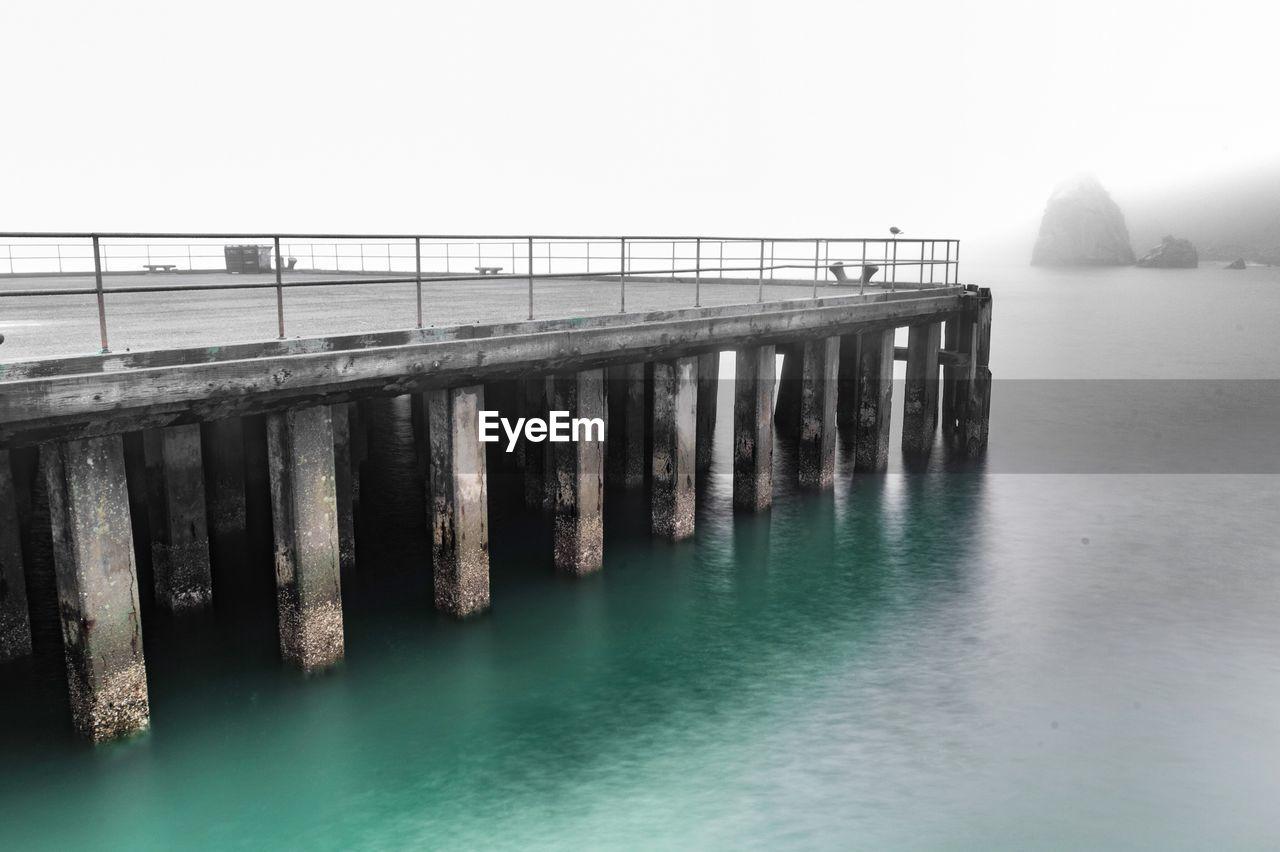 Pier Over Calm Sea Against Sky
