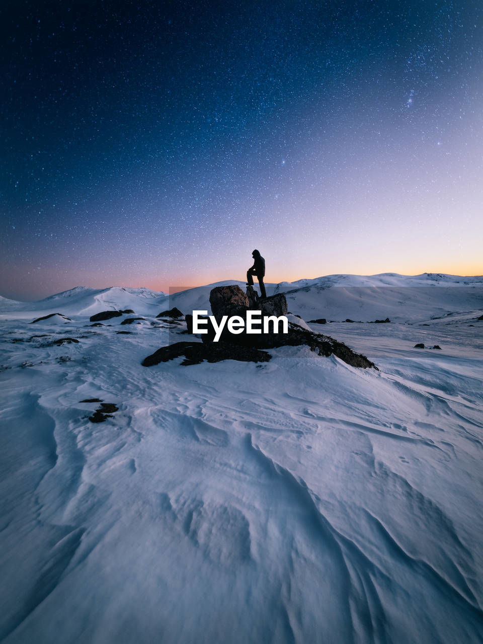 sky, real people, beauty in nature, one person, leisure activity, scenics - nature, lifestyles, nature, tranquility, cold temperature, winter, tranquil scene, star - space, astronomy, sitting, land, snow, water, outdoors
