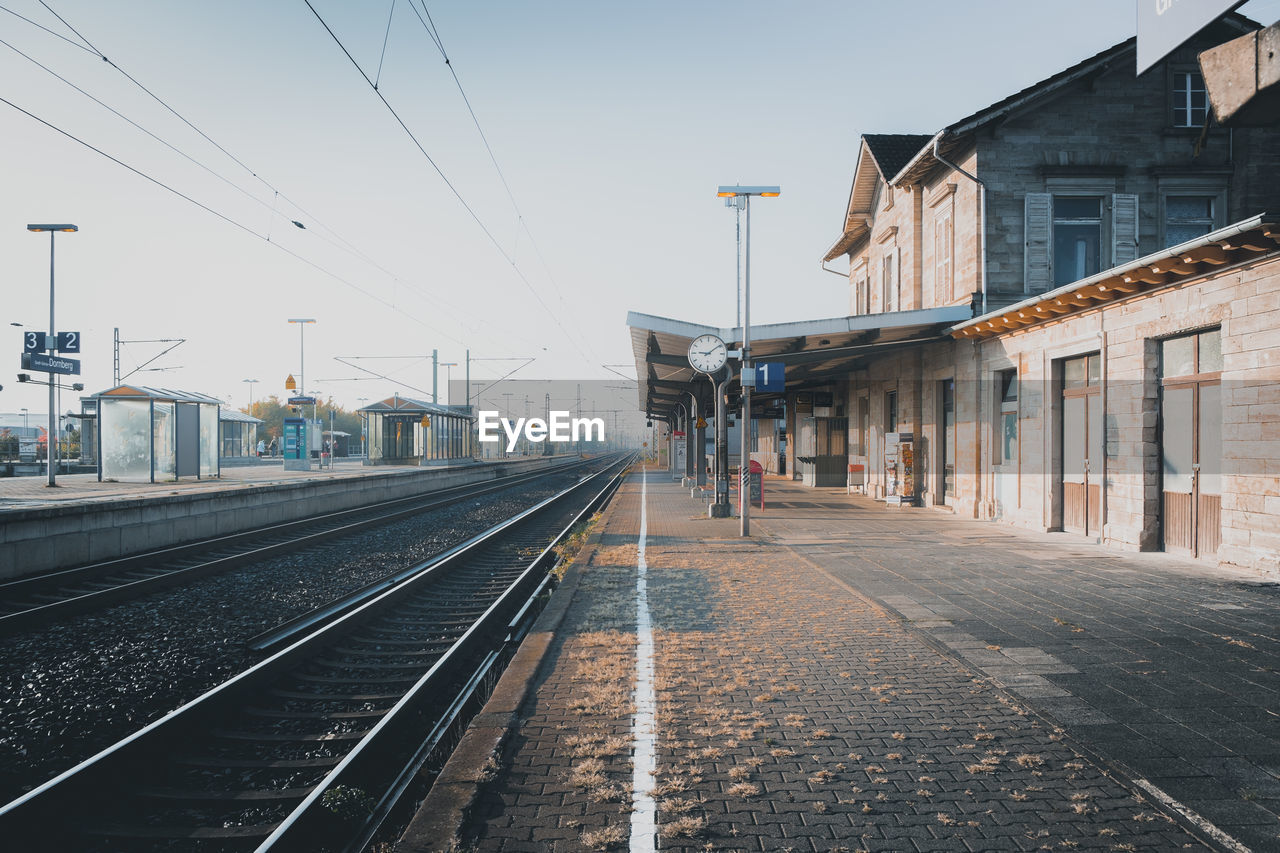 architecture, building exterior, railroad track, track, built structure, rail transportation, transportation, sky, cable, electricity, city, nature, mode of transportation, day, direction, the way forward, clear sky, technology, public transportation, power line, diminishing perspective, no people, outdoors, power supply