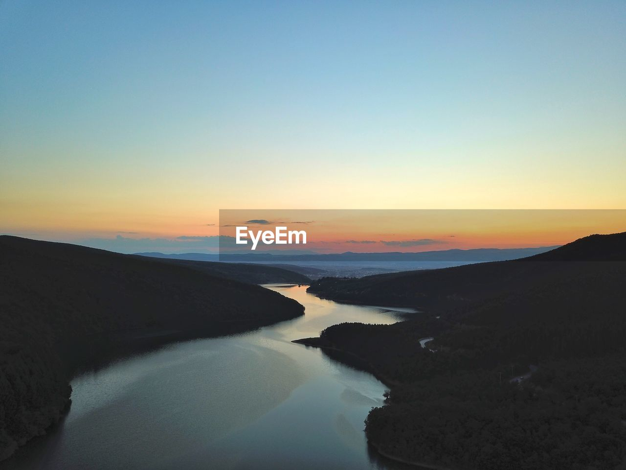 Scenic View Of River Amidst Mountain Against Sky During Sunset