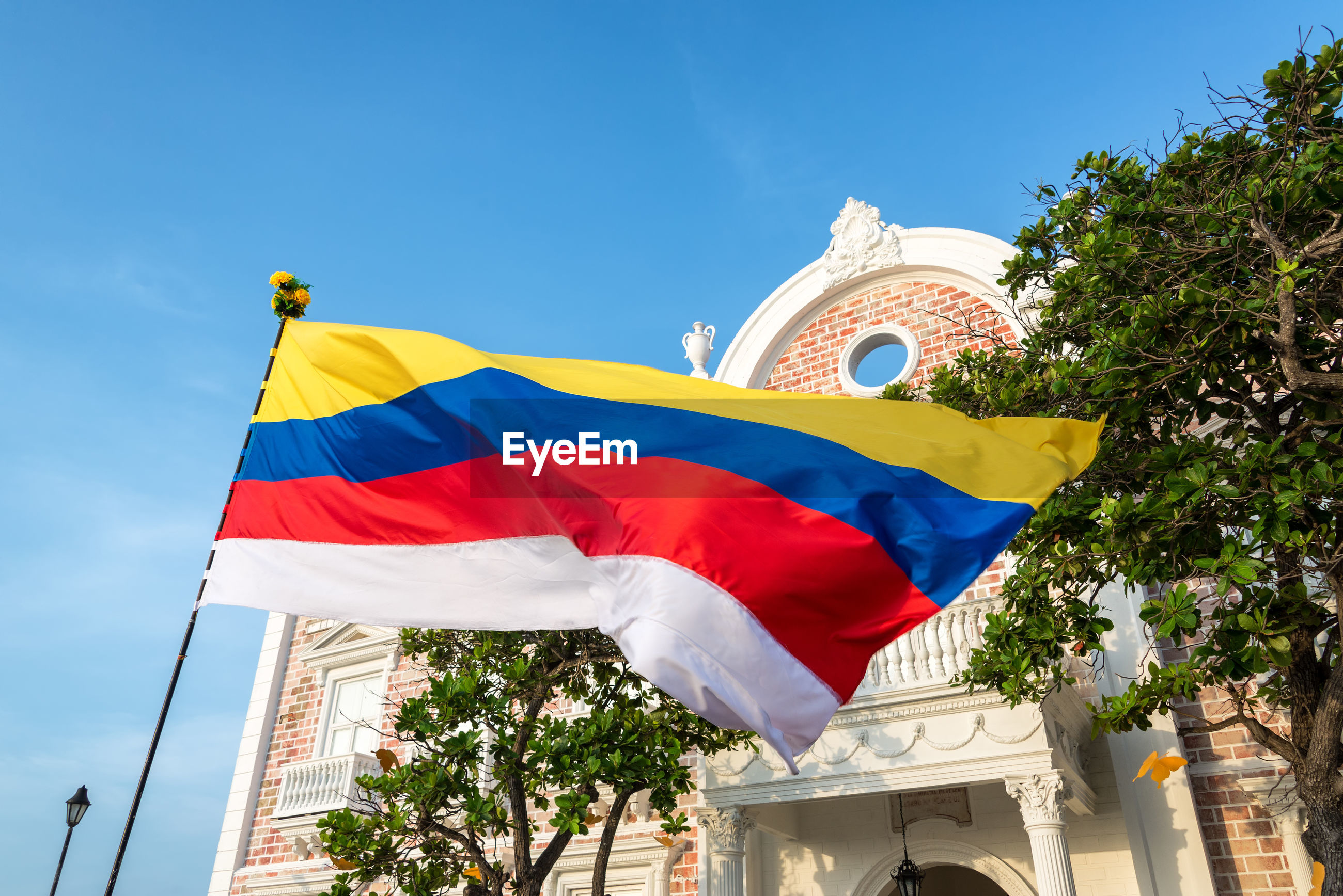 Low angle view of colombian flag waving against historic building