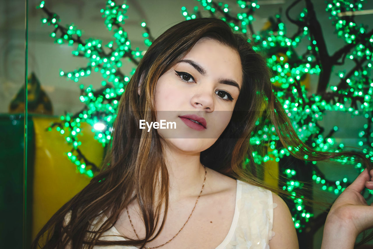 one person, green color, portrait, young adult, celebration, indoors, looking at camera, real people, happiness, christmas, christmas lights, smiling, christmas decoration, beautiful woman, young women, illuminated, tree, close-up