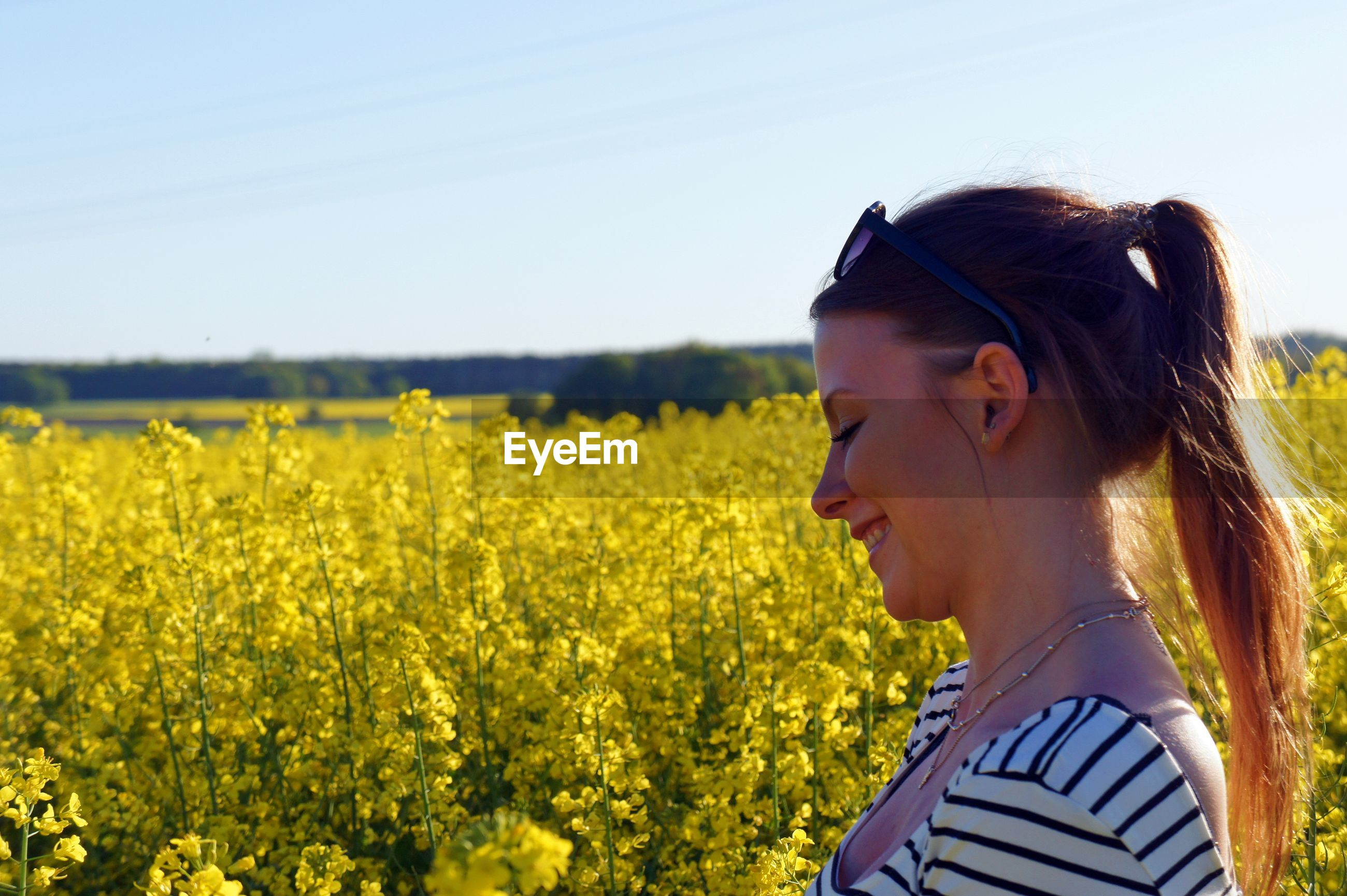 Side view of smiling woman standing amidst yellow flowering plants on field against sky during sunny day