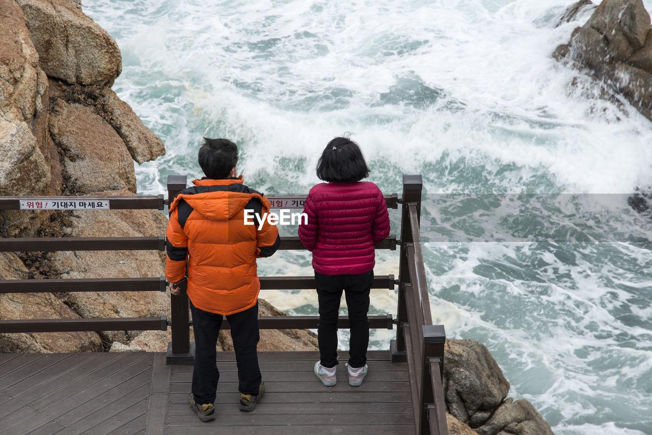 Rear View Of Siblings Standing On Bridge And Looking At Sea