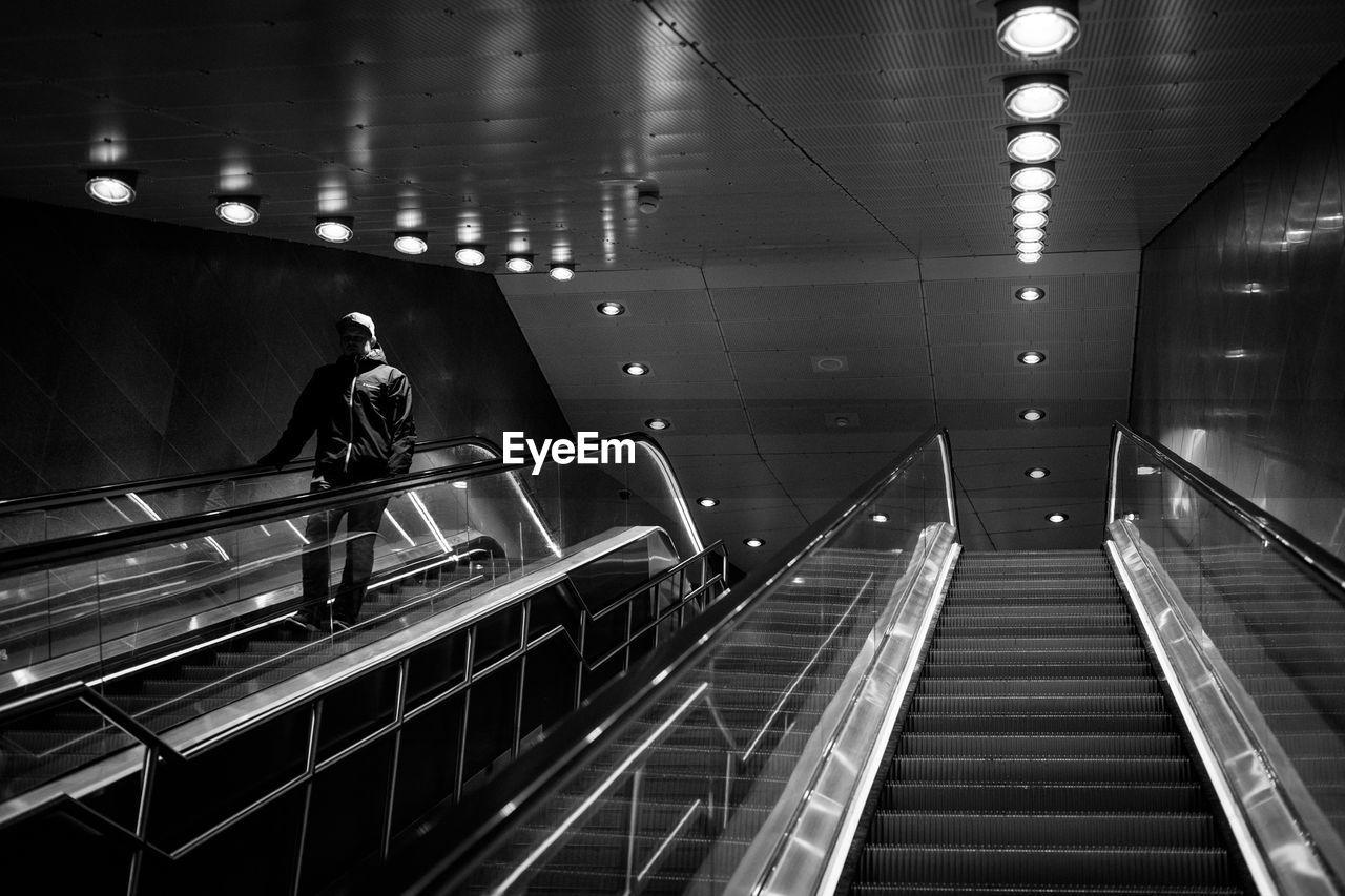 Man On Escalator At Illuminated Railroad Station