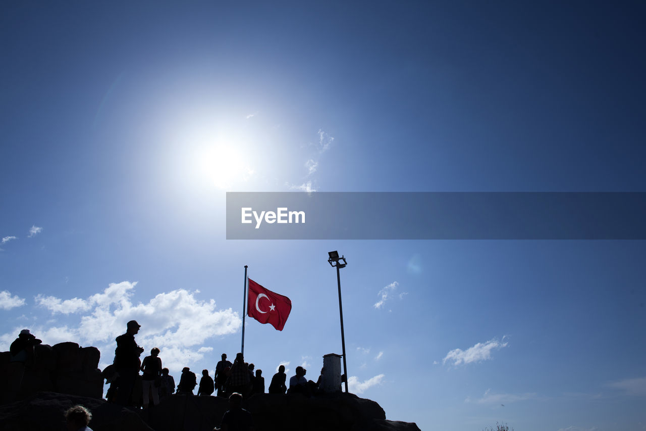 Low Angle View Of People Standing By Turkish Flag Against Sky
