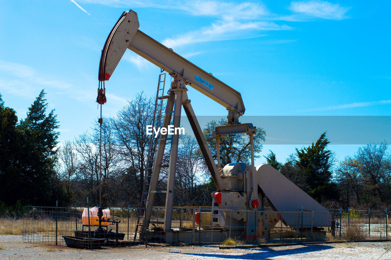 oil industry, industry, oil pump, tree, industrial equipment, sky, no people, oil well, day, outdoors, manufacturing equipment, drilling rig