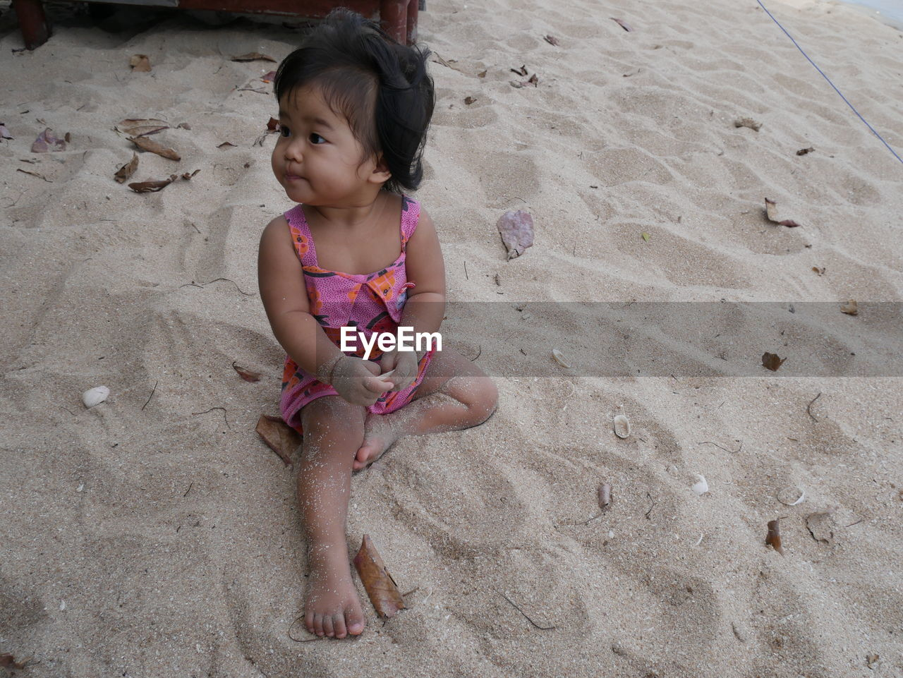 Baby girl sitting on sand at beach