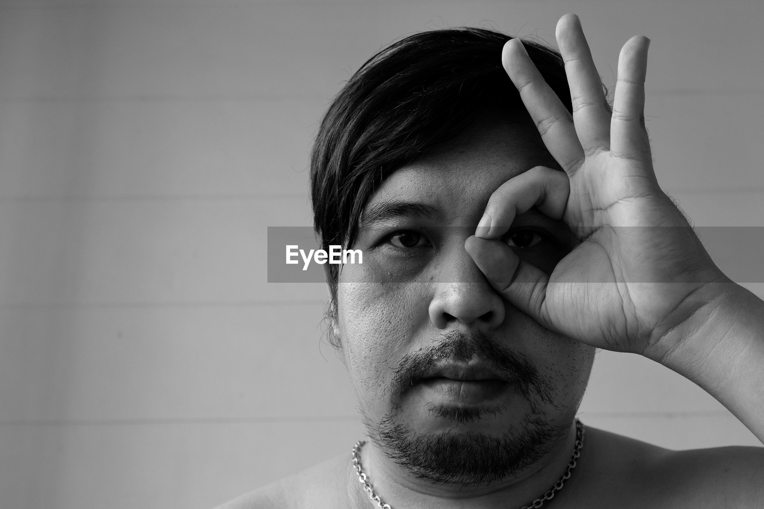 Close-up of shirtless man gesturing ok sign over eyes while looking away
