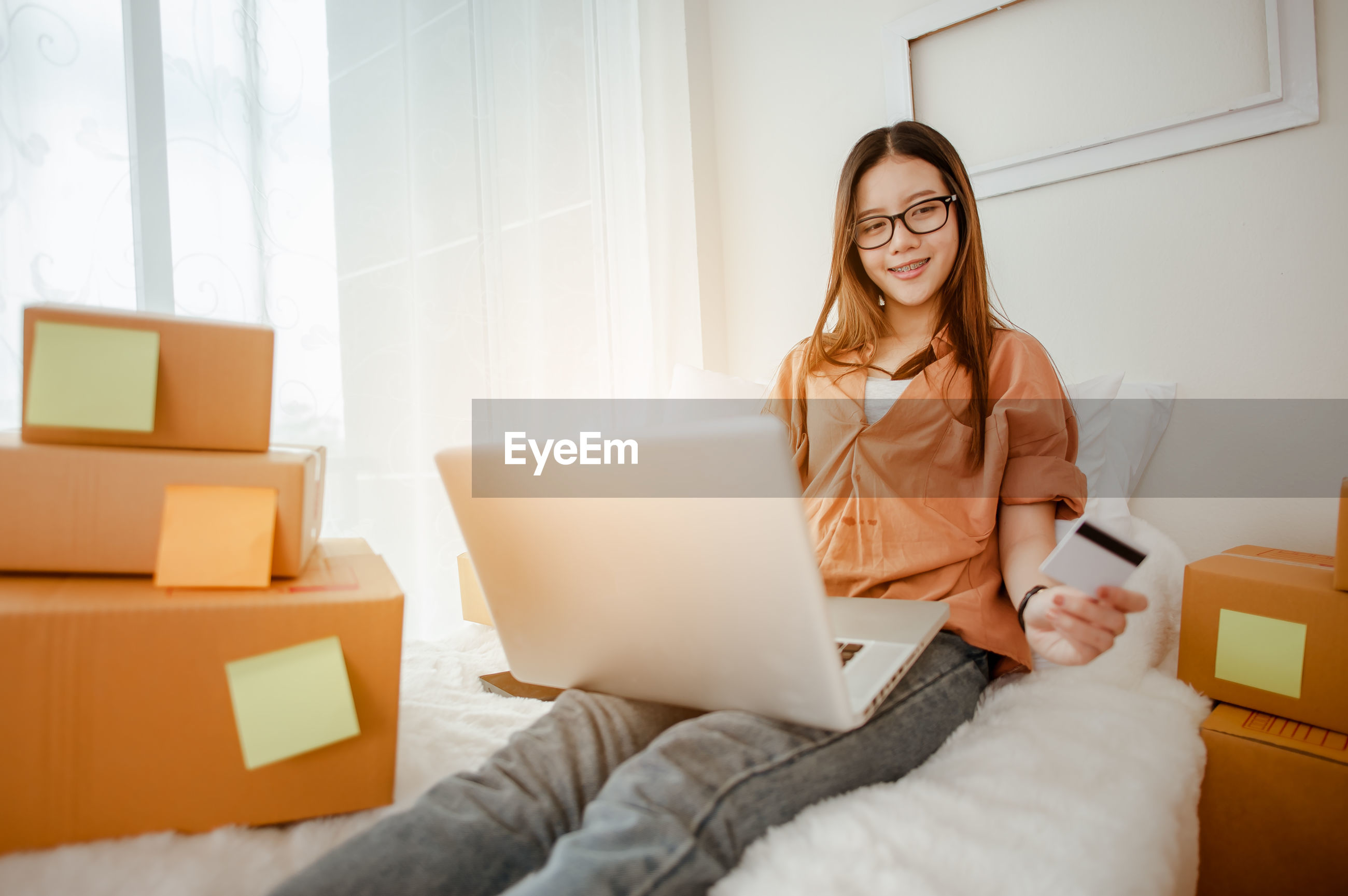 YOUNG WOMAN USING PHONE WHILE SITTING ON LAPTOP AT HOME