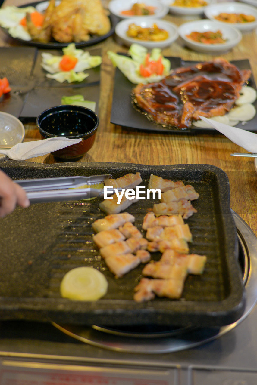 food, food and drink, freshness, one person, real people, indoors, human body part, human hand, unrecognizable person, ready-to-eat, hand, lifestyles, table, human finger, finger, plate, body part, holding, selective focus, preparation, preparing food, japanese food