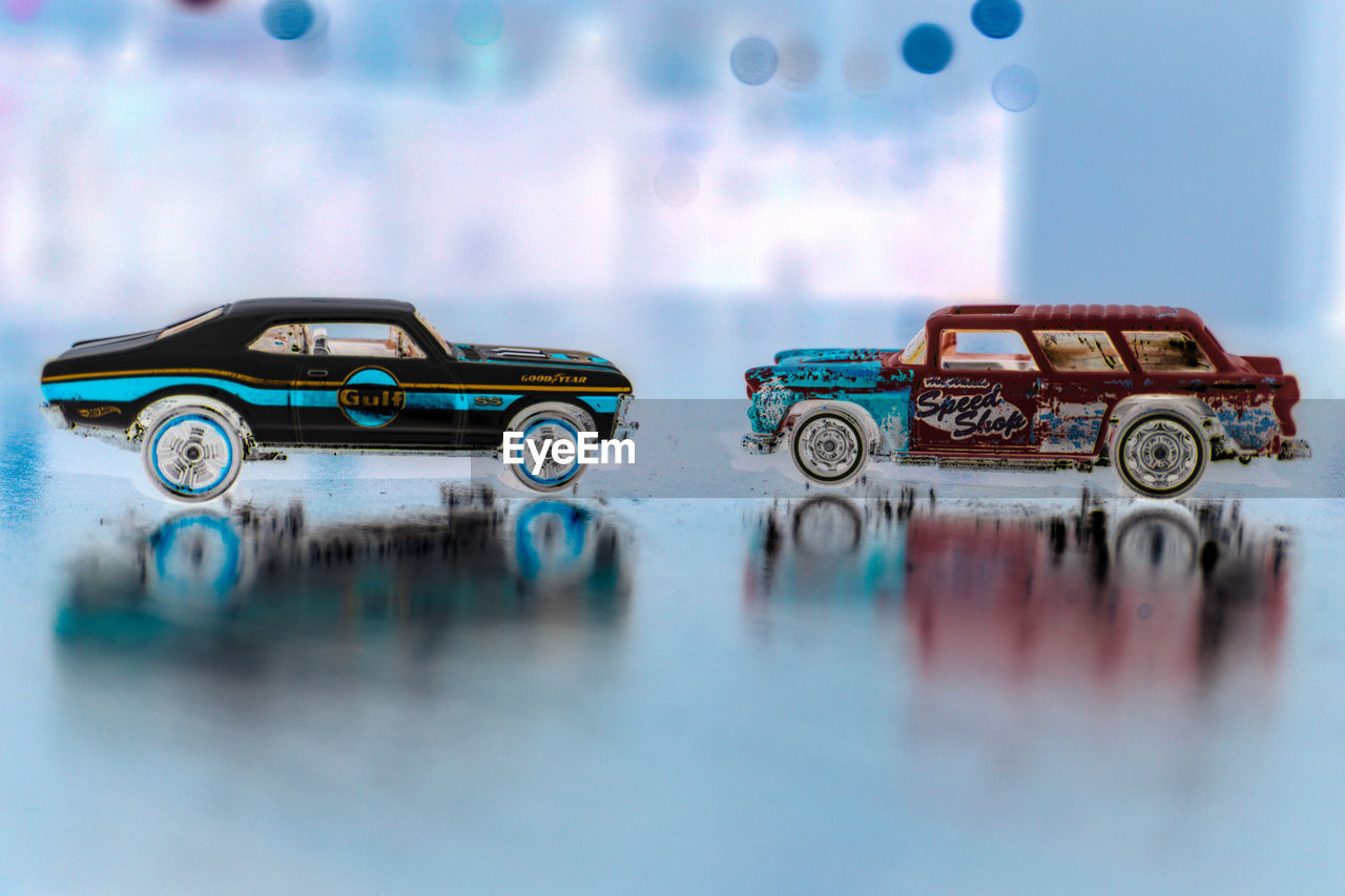 car, transportation, mode of transportation, no people, motor vehicle, toy, selective focus, land vehicle, toy car, close-up, reflection, indoors, day, metal, still life, blue