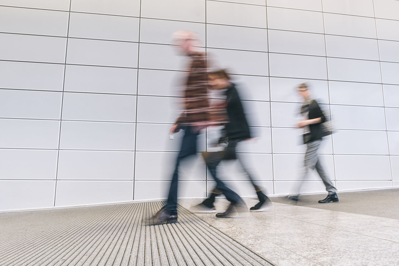 blurred motion, motion, architecture, men, real people, walking, group of people, speed, people, urgency, casual clothing, city, built structure, lifestyles, day, wall - building feature, on the move, indoors, flooring, adult