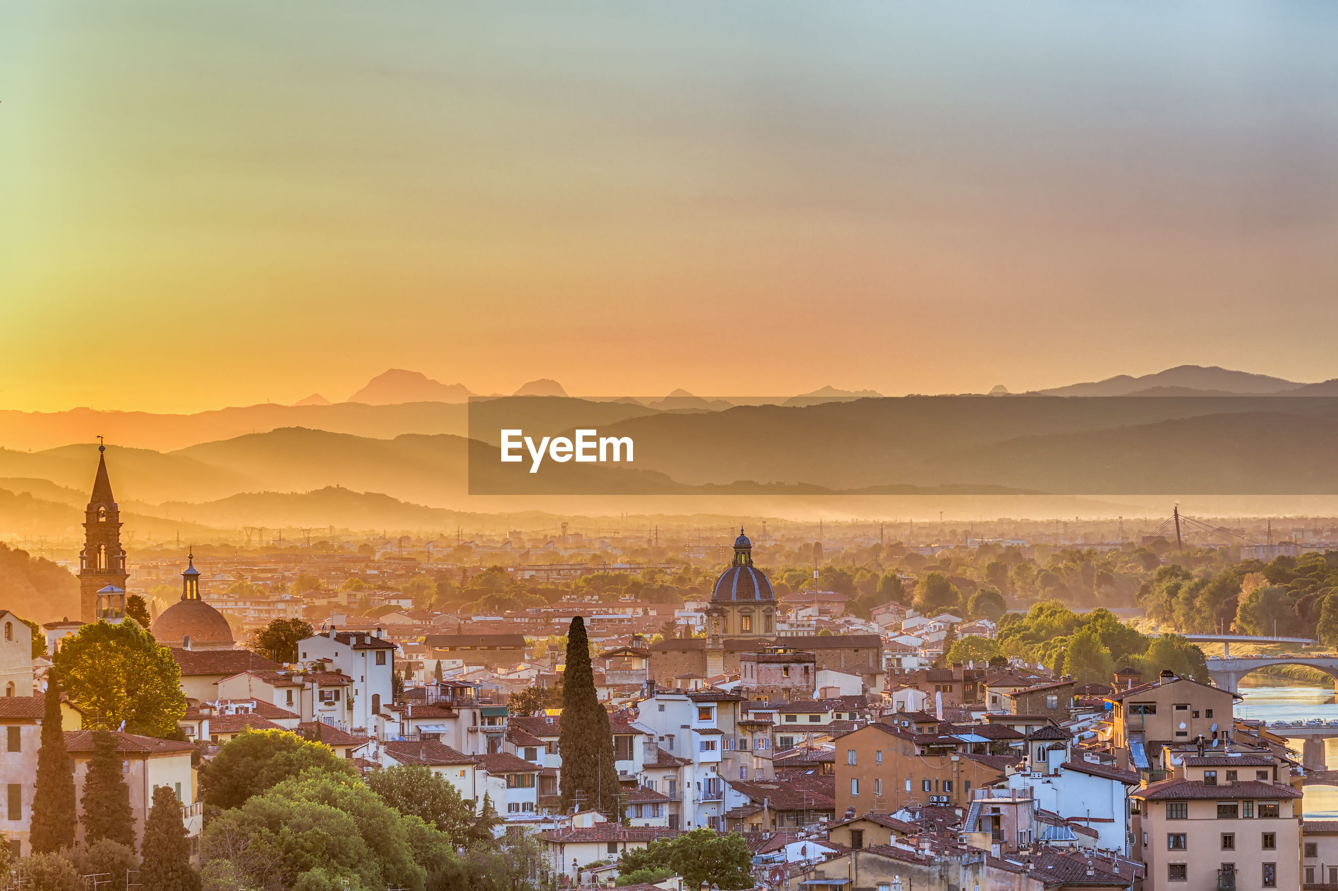 High angle view of city against silhouette mountains during sunset