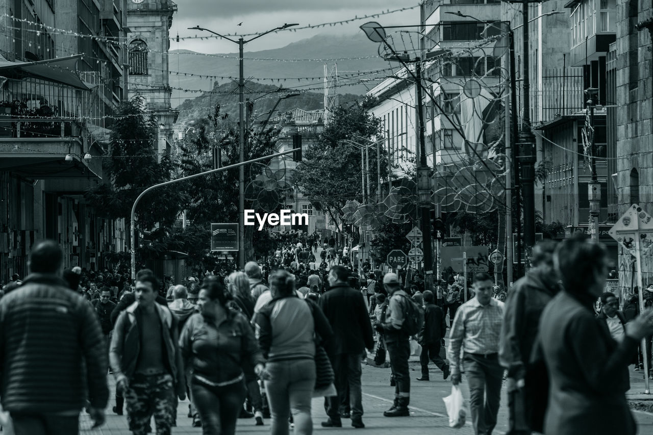 city, building exterior, architecture, built structure, street, group of people, real people, crowd, city life, men, large group of people, women, walking, lifestyles, adult, city street, outdoors, day, leisure activity, power supply