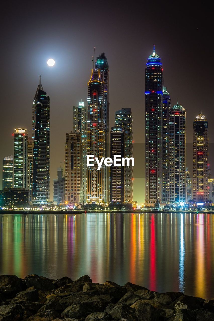 building exterior, built structure, architecture, illuminated, night, city, water, building, office building exterior, skyscraper, sky, tall - high, modern, nature, tower, urban skyline, waterfront, cityscape, office, no people, outdoors, financial district, moonlight