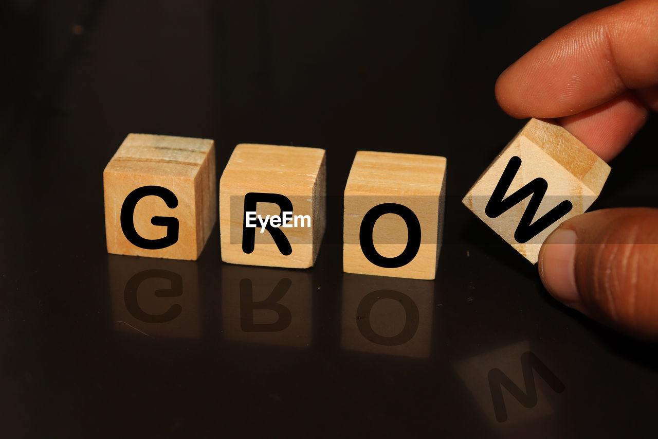 Cropped hand with grow text on toy blocks against black background