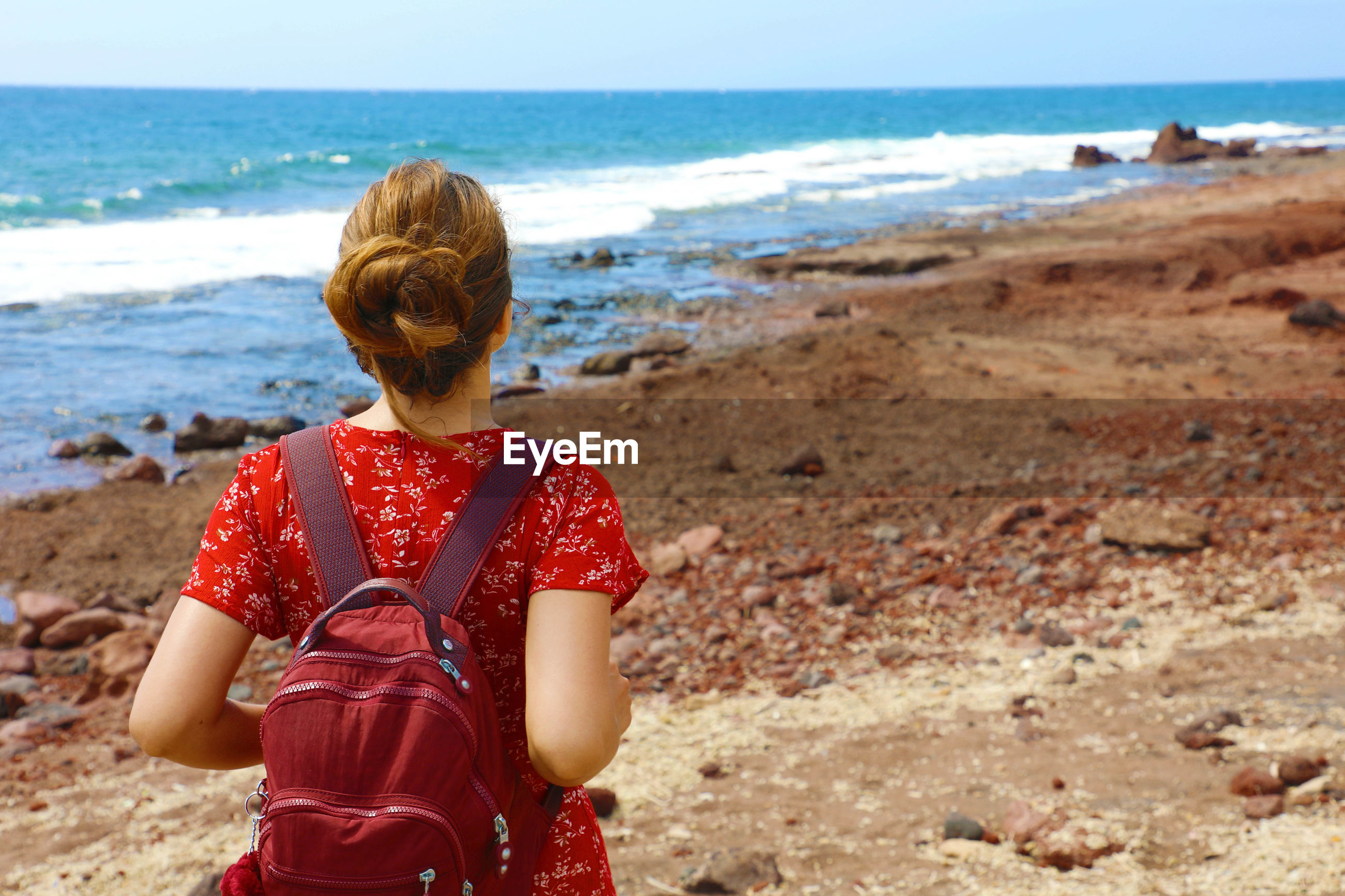 Rear view of woman with backpack standing at beach