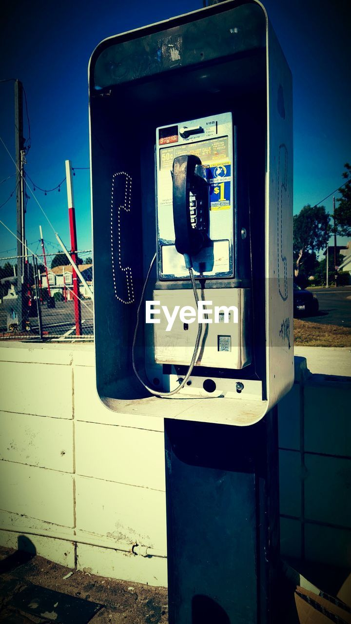 communication, telephone, connection, pay phone, telephone booth, telephone receiver, old-fashioned, outdoors, telecommunications equipment, technology, no people, day, using phone, close-up, sky