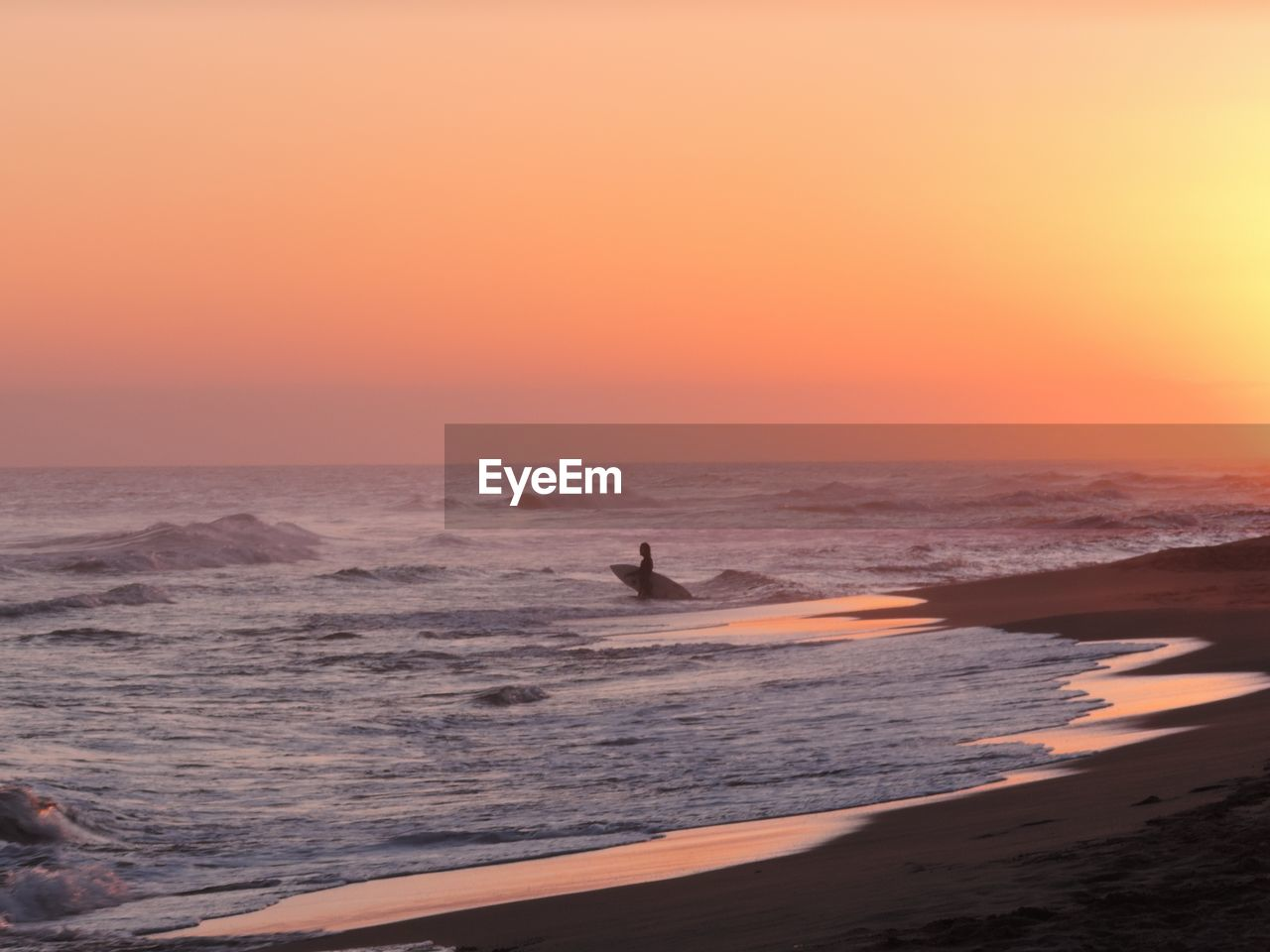 sunset, sky, sea, water, horizon over water, orange color, horizon, scenics - nature, beauty in nature, beach, land, motion, real people, wave, nature, lifestyles, aquatic sport, sport, leisure activity, outdoors