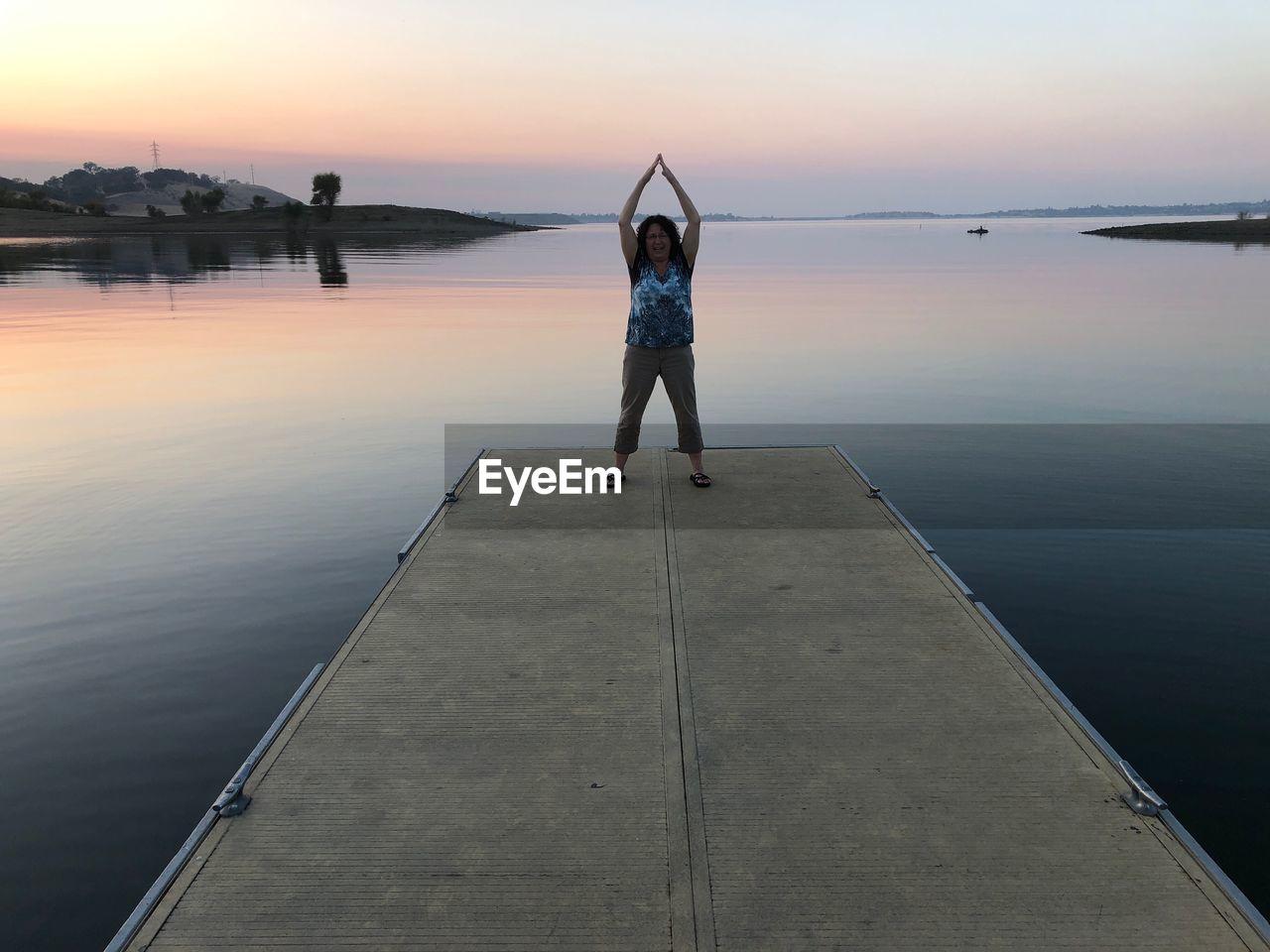 Full Length Of Woman Standing On Pier Against Sky During Sunset